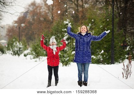 Young woman with the daughter on walk in winter day. Woman and the girl are dressed in bright down-padded coats. They throw snow up. It is snowing. All ground in the park is covered with snow.