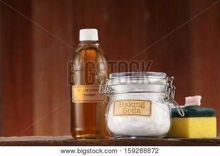 Apple cider vinegar, baking soda and cleaning sponge on wooden  background