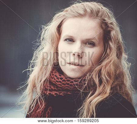 portrait of blond woman with blue eyes on a dark background winter girl in a black coat, curly hair, blond and beautiful, red scarf, light snow, cute look, half-smile, the kindness, photo on street, purple preset processing