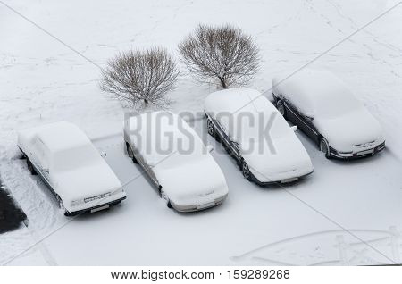 Ground parking cars after snowfall view from above. Automobiles covered with snow.
