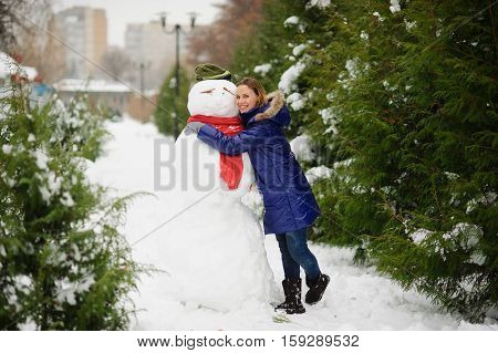 Snow-covered park. The girl in a blue down-padded coat with a hood playfully embracesa big snowman. A snowman in a cap and a scarf. It is snowing.