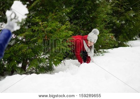 Cheerful girl of school age in a red jacket plays with someone in snowballs. She hides in bush thickets from the rival. Ground is completely covered with fluffy snow. Game gives to the child pleasure.