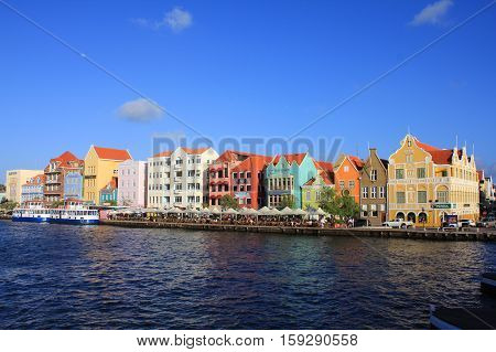 WILLEMSTAD CURACAO - FEBRUARY 11 2014: Waterfront with harbour and colorful houses in Willemstad. The city centre is UNESCO World Heritage Site.