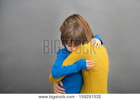 Sad Little Child, Boy, Hugging His Mother At Home, Isolated Image