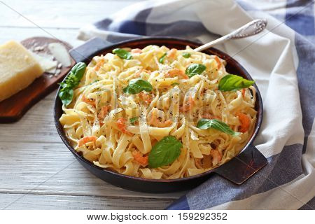 Pan with tasty alfredo pasta and napkin on wooden table
