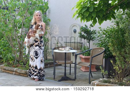 Woman in an elegant dress holding her pet - Cavalier King Charles Spaniel - standing in a garden and holding a book and a notepad