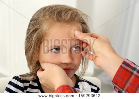 Woman applying sticking plaster to girl's forehead, close up view