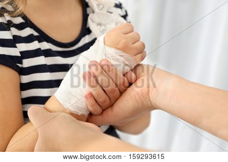 Woman wounding bandage around little girl's wrist, close up view