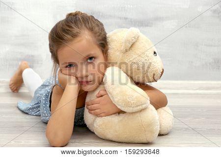 Bored girl with teddy bear lying on floor against grey wall
