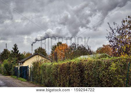 Smoking Chimney Behind Garden Plots In Berlin