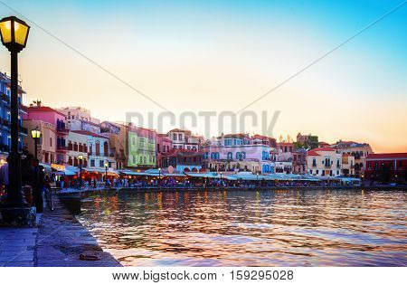 embankment and venetian habour with Turkish Mosque Yiali Tzami of Chania at colorful sunset, Crete Greece, retro toned