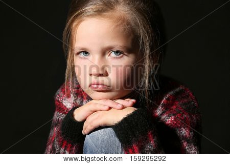 Disappointed little girl on black background, close up view