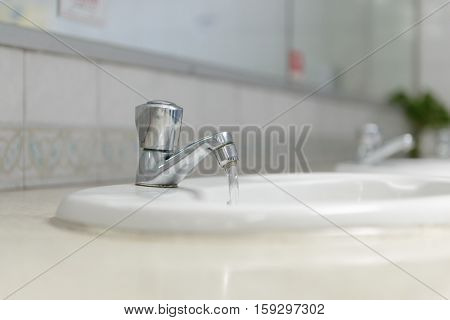 Water drop from faucet in bathroom - stock photo
