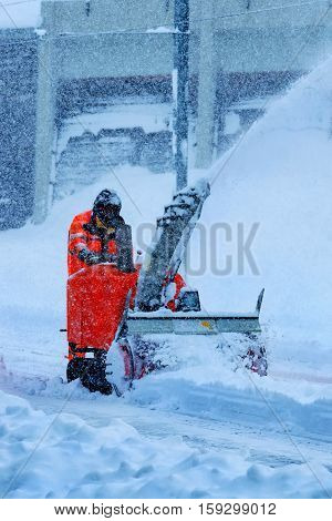 Cleaning Snow Machine or Snow thrower Machine working during snowing in Winter time