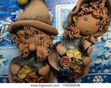 New year and Christmas. Festive New Year's gnomes - the boy and the girl with flowers. New Year's interior. Clay.