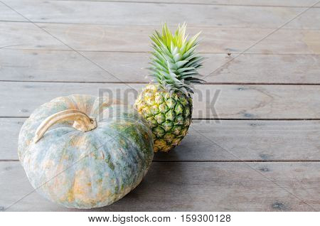 Pumpkin with pineapple placed on a wooden board with a child.
