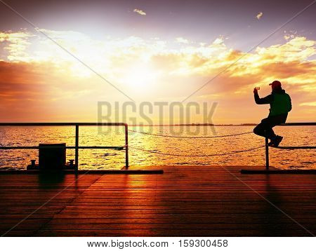 Tourist Sit On Mole Handrail And Takes Pictures. Man Enjoy Morning At Sea