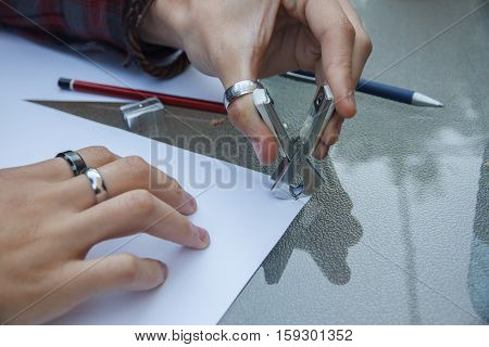 Photo of close up of a hands removing a staple from some documents with a staple remover.