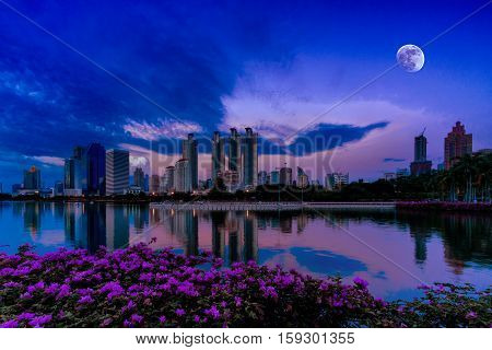 Night Cityscape with Business buildings Light and reflection on the water with moon on the sky from Benjakiti park Bangkok Thailand