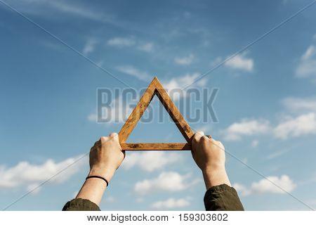 Hands Holding Triangle Symbol Cloudscape Concept