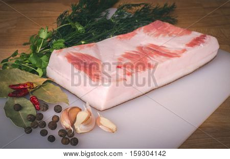 Fresh raw pork fat ready for gammoning on wooden cutting board, spices and herbs. Whole uncooked pork fat prepare for salting. Large piece of fresh pork fat.