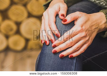 Woman sitting indoors with her hands on knee. Young woman wears green sweater and blue denim jeans. Fingernails with beautiful fresh red manicure. Close up horizontal color photo.