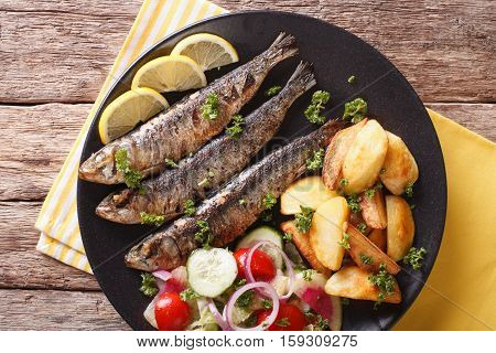 Fried Sardines With Potatoes And Fresh Vegetable Salad Close-up. Horizontal Top View