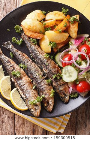 Fried Sardines With Roasted Potatoes And Fresh Salad Closeup. Vertical Top View