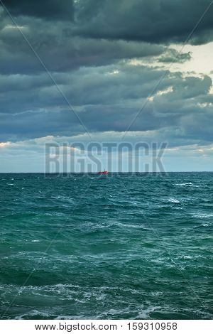 Marine vertical landscape. Sea storm. Gloomy sky with clouds. In the middle of a landscape far away is the red ship, boat, barge. Dark blue sea, gray clouds.