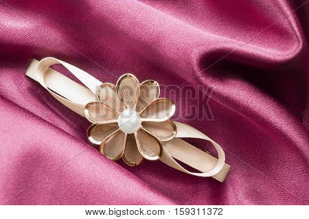 Golden floral barrette on pink satin as a background