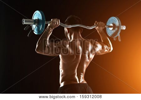 Rear view studio shot of a bodybuilder lifting a barbell on black background. with sun flare