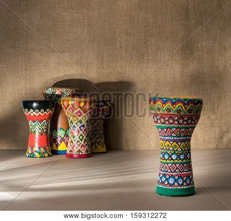 Front view of decorated colorful pottery goblet drum on background of goblet drums wooden table with vanishing shadow lines and sackcloth wall. Low light studio shot