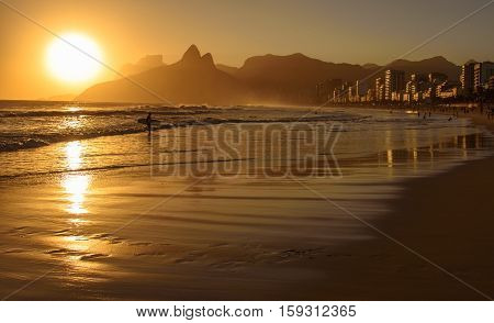 Golden sunset with Two Brothers Dois Irmaos Mountain and surfer silhouette at Ipanema Beach, Rio de Janeiro, Brazil