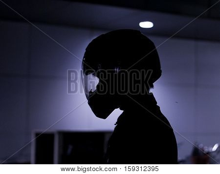 motorcyclist biker rider  wearing helmet in shadow