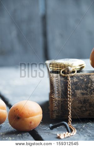 food background - ripe apricots on a vintage table, pocket watch and book