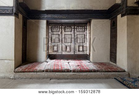 Cairo, Egypt - November 19, 2016: Interleaved wooden window (Mashrabiya) with built-in couch and an embedded wooden cupboards at El Sehemy house an old Ottoman era house in Cairo originally built in 1648