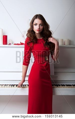 Woman In Evening Red Dress Standing Next To A Large White Grand Piano