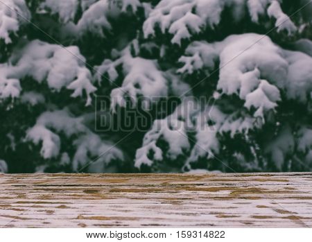 empty wooden table on a background of snow-covered trees tinted photo