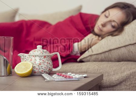 Sick woman covered with a blanket lying in bed with high fever and a flu resting. Teapot pills and lemon on the table focus on the teapot