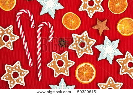 Christmas and new year holiday frame, made with sweets, stars, dried oranges, heart, cinnamon, beautiful ginger snaps - snowflakes and spices on red background. Flat lay style.