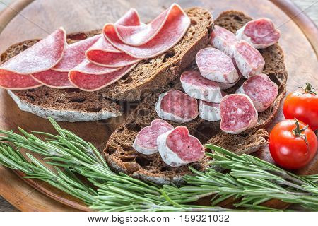 Sandwiches with dark-rye bread and different kinds of salami