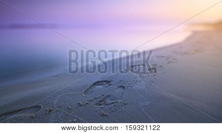Early morning. Footprints in the sand along the seashore.