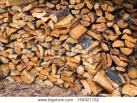 Larch wood for the stove, stacked under a canopy