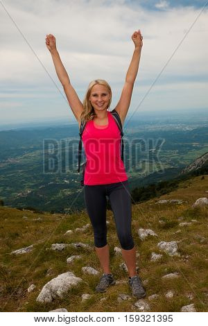 Trekking - Woman Hiking  In Mountains On A Calm Sumer Day Being Happy And Rises Arms As She Reaches
