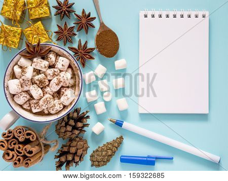 Hot Drink With Marshmallow And And Notebook On Blue Background