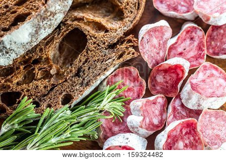 Fuet with dark-rye bread and fresh rosemary