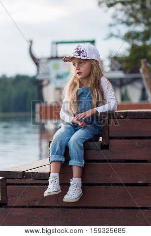 cute girl preschooler summer evenings resting on the lake