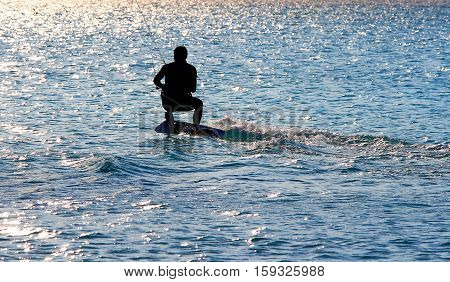 Kite surfing at sunset. Silouette of kite surfer.