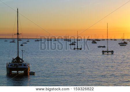 Catamarans in a bay at sunset over sea. Darwin Australia