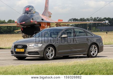 VOLKEL NETHERLANDS - JUN 15 2013: Audi A6 Limousine driving in front of a Dutch F-16 fighter jet during the Royal Netherlands Air Force Open Day.